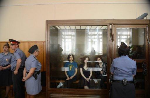 "Members of a female punk band ""Pussy Riot"" Nadezhda Tolokonnikova (L), Maria Alyokhina (C) and Yekaterina Samutsevich (R), sit inside a glass enclosure during a court hearing in Moscow on August 8, 2012. The three band members are on trial for hooliganism motivated by religious hatred"