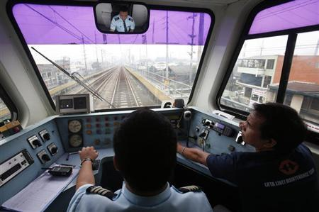 A maintenance man sits next to a train operator as they travel on Southeast Asia's first light rail transit (LRT) network, which is 29-years-old, in Manila October 11, 2013. REUTERS/Erik De Castro