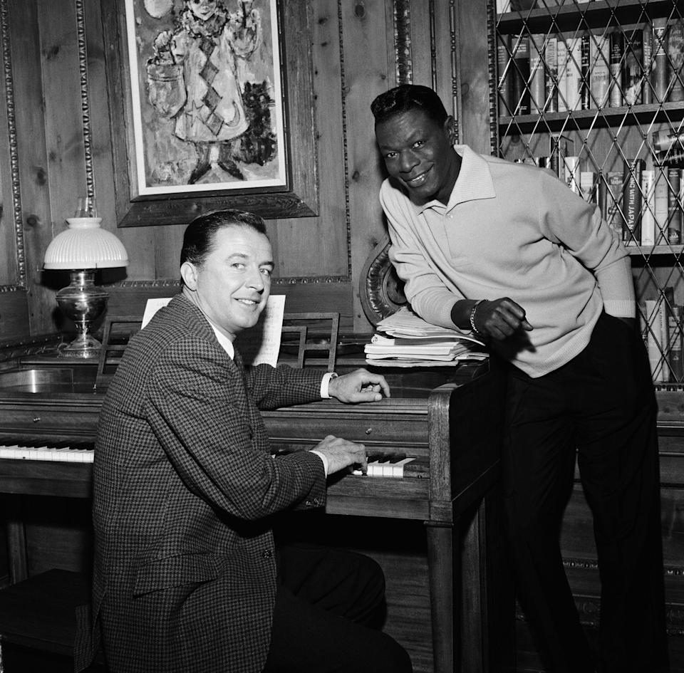 """<p>Television host Dean Miller visits the home of Nat King Cole in 1961. Cole moved his family to the Los Angeles neighborhood in 1948, a decision which led to death threats and discrimination, as the neighborhood was predominately white at the time. """"I was oblivious to all that. I felt like royalty living in our home,"""" the singer's daughter, Natalie Cole, wrote in <a href=""""https://www.wsj.com/articles/natalie-cole-an-unforgettable-dream-house-1401298798"""" rel=""""nofollow noopener"""" target=""""_blank"""" data-ylk=""""slk:The Wall Street Journal in 2014"""" class=""""link rapid-noclick-resp""""><em>The Wall Street Journal</em> in 2014</a>. </p>"""