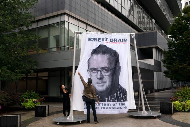 An image of federal bankruptcy judge Robert Drain is installed by protesters in front of Purdue Pharma's headquarters (Mark Lennihan/AP)