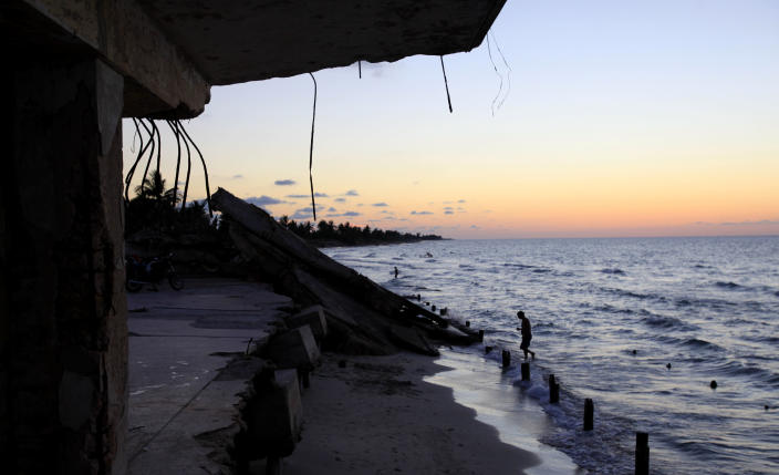 In this May 24, 2013 photo, a man walks in the water near the remains of a destroyed school along the shore of Havana, Cuba. Even the very existence of climate change may be a matter of political debate on Capitol Hill, but for low-lying Cuba, calculations have spurred systemic action. Cuba's government has changed course on decades of haphazard coastal development, which threatens sand dunes and mangrove swamps that provide the best natural protection against rising seas. (AP Photo/Franklin Reyes)