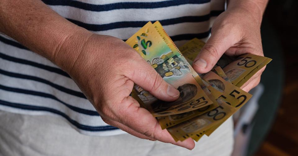 Hands holding $50 notes