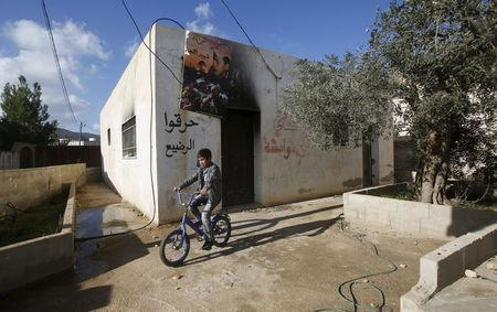 A Palestinian boy rides his bicycle past the Dawabsheh family house near the West Bank city of Nablus, December 3, 2015. REUTERS/Abed Omar Qusini