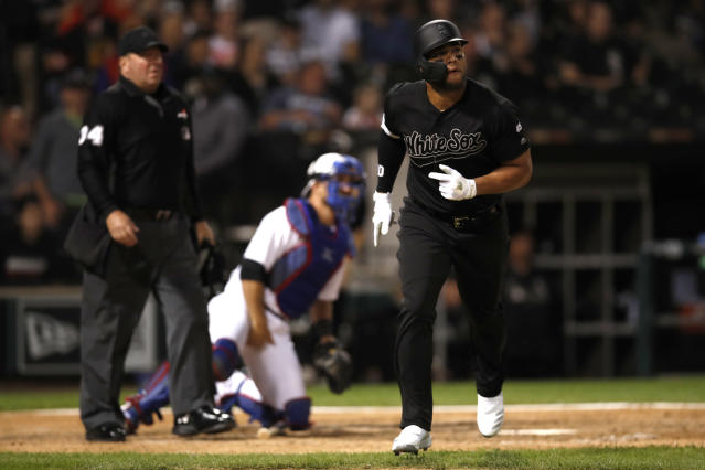 Chicago White Sox's Yoan Moncada, right, watches his two-run home run as Texas Rangers catcher Jeff Mathis, center, and home plate umpire Sam Holbrook, left, look on during the sixth inning of a baseball game Friday, Aug. 23, 2019, in Chicago. (AP Photo/Jeff Haynes)