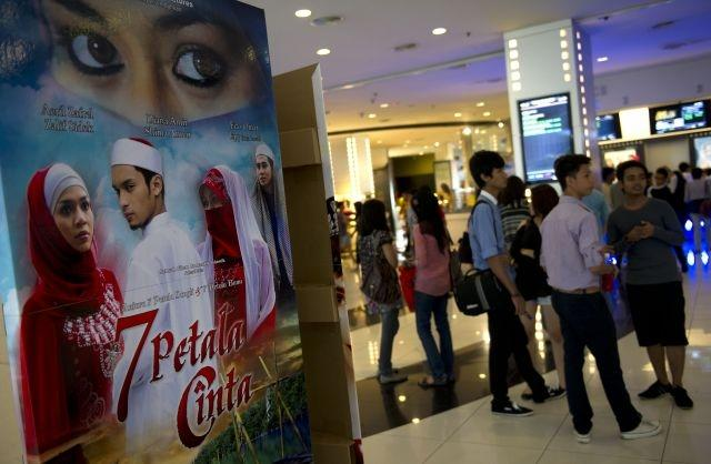 Malaysian moviegoers wait in queue to get tickets at a movie theater in downtown Kuala Lumpur