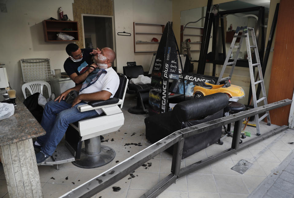 A Lebanese barber shaves the beard of a customer, at a men salon that damaged by last week's explosion that hit the seaport of Beirut, in the middle of a damaged street at Mar Mikhael neighborhood, in Beirut, Lebanon, Friday, Aug. 14, 2020. (AP Photo/Hussein Malla)