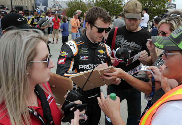 "<a class=""link rapid-noclick-resp"" href=""/nascar/sprint/drivers/396/"" data-ylk=""slk:Kasey Kahne"">Kasey Kahne</a> signs autographs for fans as he prepares to participate in qualifying for a NASCAR Cup series auto race in Fort Worth, Texas, Friday, April 6, 2018. (AP Photo/Tony Gutierrez)"