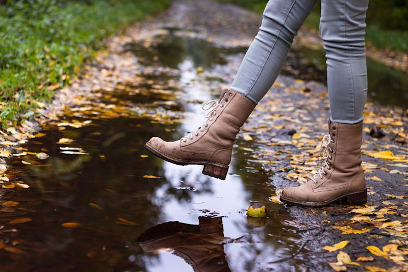 Hiking boot at autumn season. Woman walking on wet footpath after rain