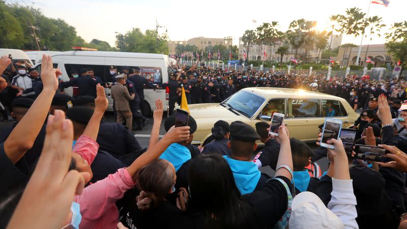 A car in the royal motorcade with Queen Suthida and Prince Dipangkorn drives past a group of anti-government demonstrators in front of the Government House, on the 47th anniversary of the 1973 student uprising, in Bangkok