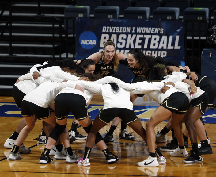 The Wake Forest team cheers before the start of the first half of a college basketball game against Oklahoma State in the first round of the women's NCAA tournament at the Greehey Arena in San Antonio, Texas, Sunday, March 21, 2021. (AP Photo/Ronald Cortes)