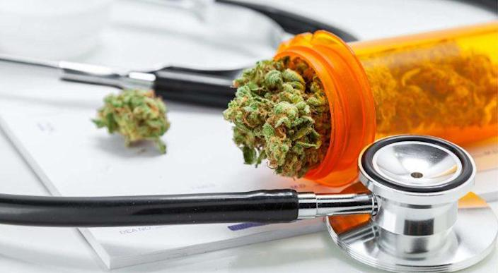 marijuana falling out of a prescription container next to a stethoscope