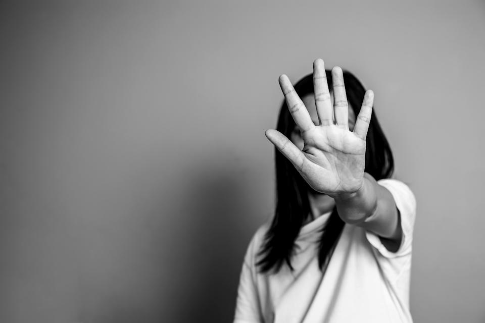 Woman raising a hand in front of her face.