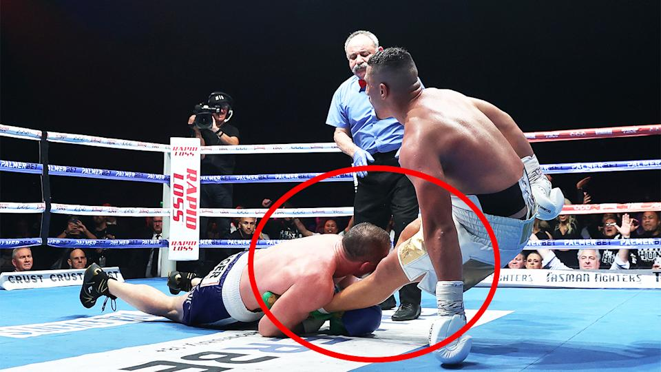 Paul Gallen (pictured left) wraps his hands around the legs of Justis Huni (pictured right) and tackles him.