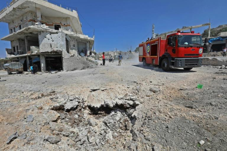 A picture taken on September 4, 2018 shows a fire engine driving on a damaged road after a reported Russian air strike in the rebel-hold town of Muhambal, about 30 kilometres southwest of the city of Idlib