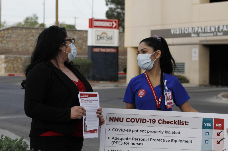 Nurses Tishna Soto, left, and Lizette Torres speak to reporters as they prepare a protest outside their work at the Las Palmas Del Sol Medical Center, Wednesday, April 1, 2020, in El Paso, Texas. Torres and Soto are members of National Nurses United, and were joined in calling for increased transparency and safety measures by members in other states. Tensions are running high at U.S. hospitals as medical systems in New York, Washington and Louisiana are shouldering an influx of patients with COVID-19 and workers lack protective gear. (AP Photo/Cedar Attanasio)