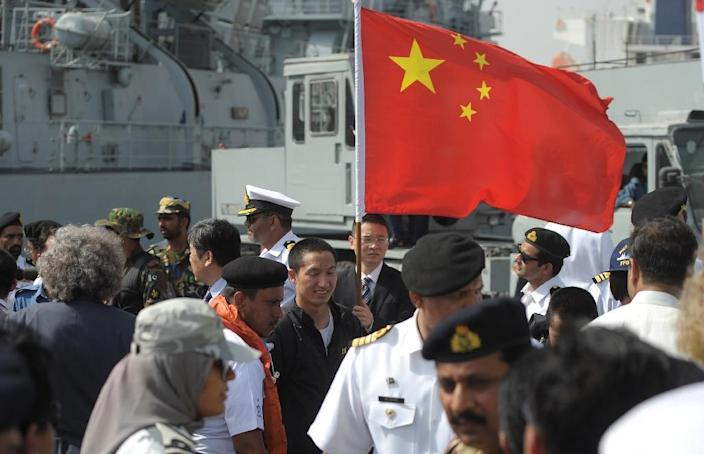 A Chinese evacuee from Yemen holds his national flag after disembarking from a Pakistan Navy ship on their arrival at Karachi port on April 7, 2015 (AFP Photo/Rizwan Tabassum)