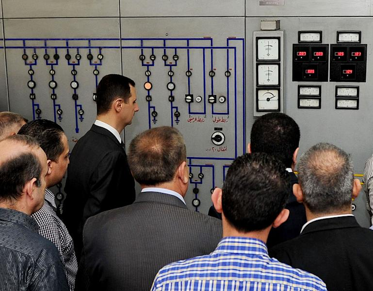 In this photo released by the Syrian official news agency SANA, President Bashar Assad, left, visits the Umayyad Electrical Station on May Day, a day after a powerful bomb hit the capital. in Damascus, Syria, Wednesday, May 1, 2013. (AP Photo/SANA)