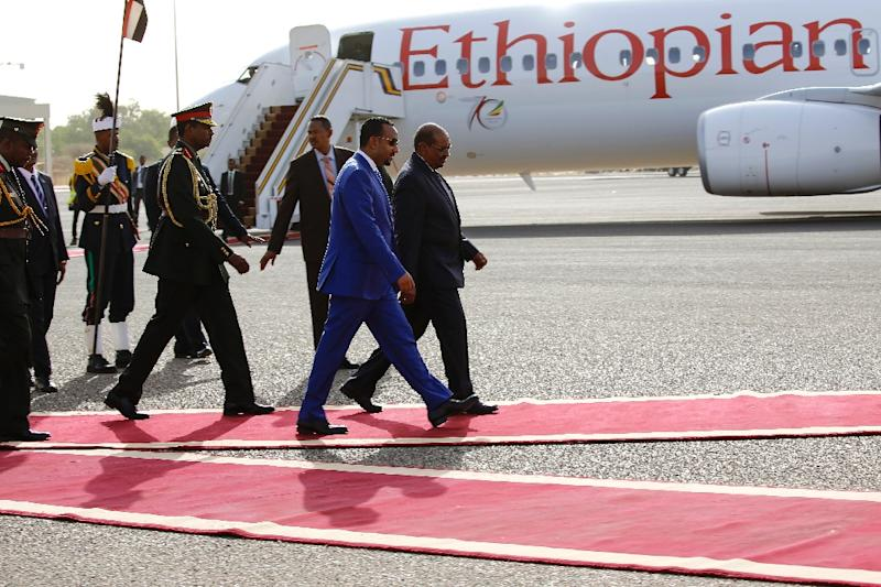 Prime Minister Abiy Ahmed, pictured in a blue suit, has decided to sell shares in the national carrier Ethiopian Airlines