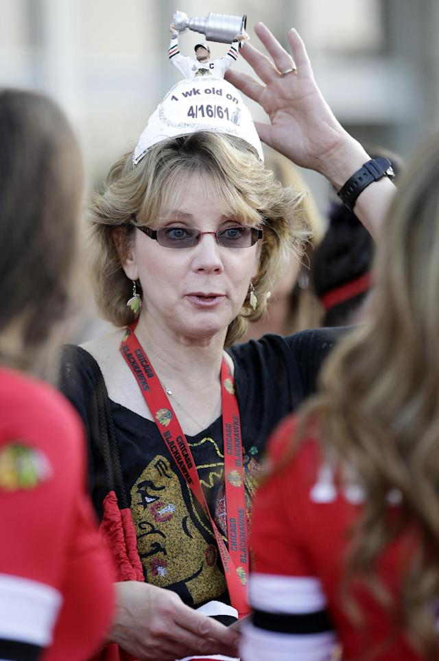 A Chicago Blackhawks fan Elain Waterhouse talks with members of the Blackhawks Ice Crew as she waits for a red carpet event in front of the United Center before a season opener NHL hockey game between the Washington Capitals and the Blackhawks on Tuesday, Oct.1, 2013, in Chicago. (AP Photo/Nam Y. Huh)