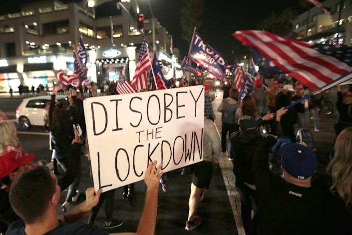 Huntington Beach, CA, Saturday, November 21, 2020 - As Covid-19 cases reach record numbers in the U.S. and California, hundreds gather at the pier and Pacific Coast Highway to protest a State mandated curfew of 10 pm. (Robert Gauthier/ Los Angeles Times)