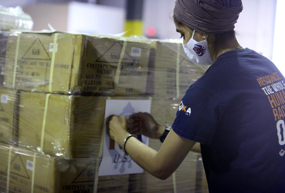 Dr. Abhu Kaur of Khalsa Aid USA, a global humanitarian organization, labels a pallet of electrical transformers, which will be shipped to New Delhi with oxygen concentrators this week on New York's Long Island, Friday, May 7, 2021. With teams deployed in India to help support COVID-19 patients, Khalsa Aid USA plans to provide a total of 500 oxygen concentrators and 500 transformers to cities throughout the country. (AP Photo/Jessie Wardarski)