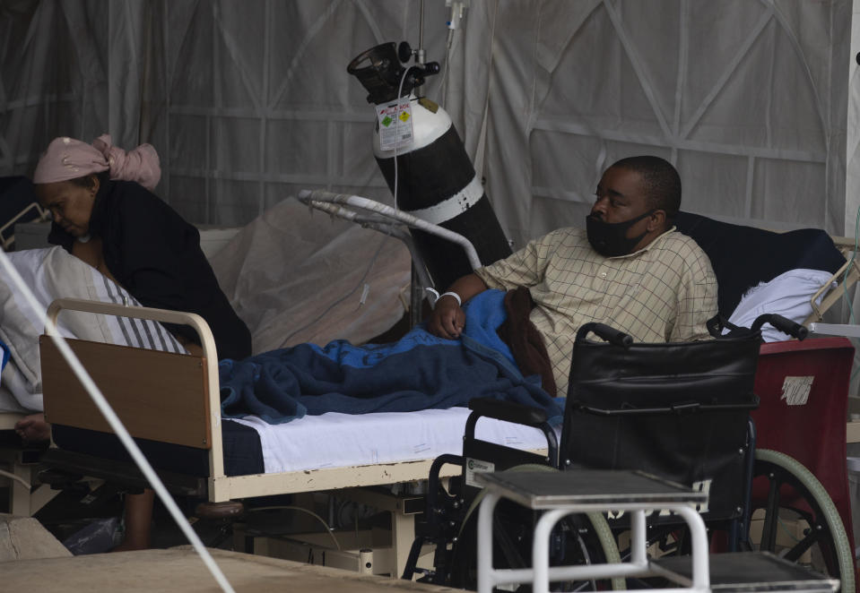 A patient lays in his bed at the Steve Biko Academic Hospital's outside parking area in Pretoria, South Africa, Monday, Jan. 11, 2021. As the numbers of new confirmed cases rise, South Africa's hospitals are exceeding capacity, according to health officials. (AP Photo/Denis Farrell)