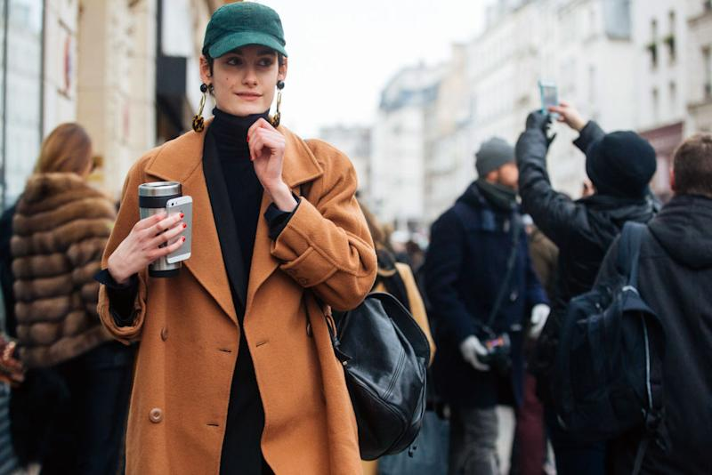 PARIS, FRANCE - JANUARY 25: A model holds an iPhone and thermos after the Jean Paul Gaultier show and wears a green cap, earrings, and a camel peacoat during Couture Spring/Summer 2017 Fashion Week on January 25, 2017 in Paris, France. (Photo by Melodie Jeng/Getty Images)
