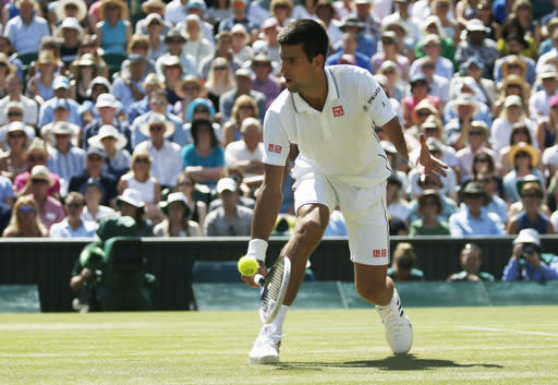 Novak Djokovic of Serbia plays a return to Grigor Dimitrov of Bulgaria during their men's singles semifinal match at the All England Lawn Tennis Championships in Wimbledon, London, Friday, July 4, 2014. (AP Photo/Pavel Golovkin)