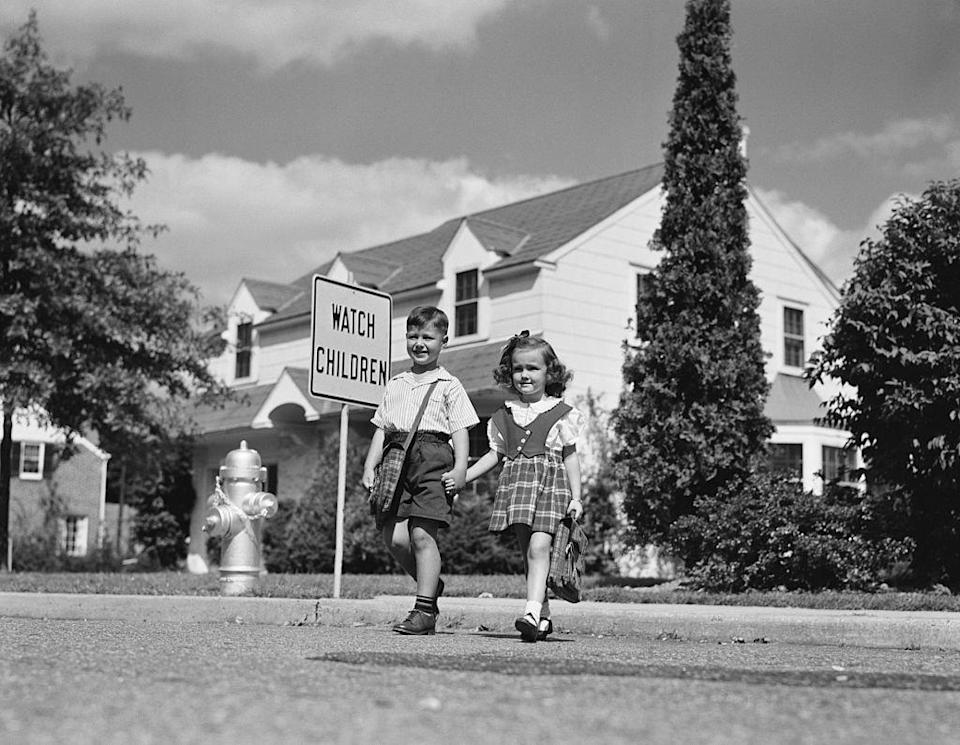 <p>A boy and girl hold hands as they walk to school.</p>