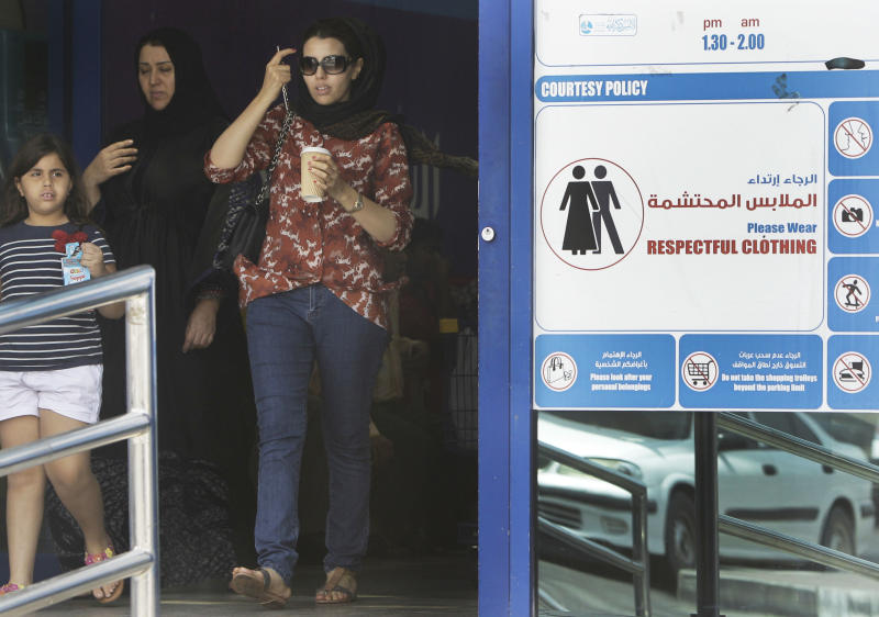 In this photo taken Monday, June 25, 2012, Women walk out a shopping mall as they pass by a dress code sign in Dubai , United Arab Emirates. As the numbers of foreigners have increased, so have the stories of them violating the UAE's strict indecency code which limits drinking to bars and nightclubs and bans public displays of affection. (AP Photo/Kamran Jebreili)