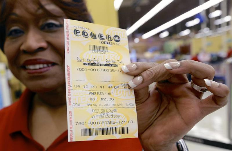 FILE - In this May 15, 2013, file photo Dean Davis displays the Powerball ticket she bought in Omaha, Neb., Wednesday, May 15, 2013. No one matched the winning numbers in Wednesday's $360 million jackpot which has now soared to $475 million, making it the second largest in Powerball history and the third biggest overall. The next drawing will be held Saturday. (AP Photo/Nati Harnik)