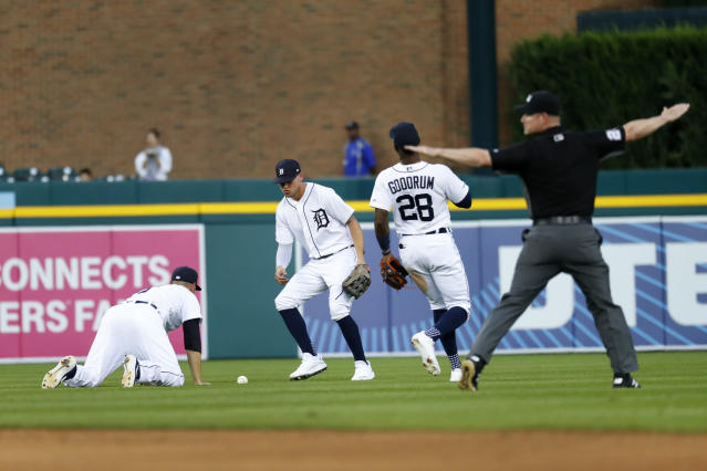 Detroit Tigers shortstop Jordy Mercer looks at the ball on his knees after a Chicago White Sox's Ryan Goins fly ball as JaCoby Jones (21) and Niko Goodrum (28) run to help in the fourth inning of a baseball game in Detroit, Monday, Aug. 5, 2019. (AP Photo/Paul Sancya)