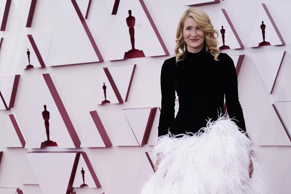 Laura Dern wears a dress with a black turtleneck top and white feathery skirt