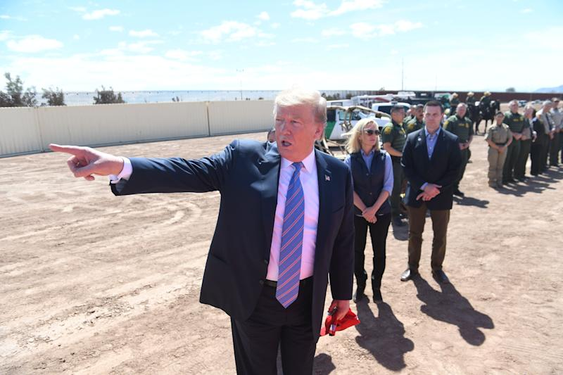 US President Donald Trump speaks with members of the US Customs and Border Patrol as he tours the border wall between the United States and Mexico in Calexico, California on April 5, 2019. - President Donald Trump landed in California to view newly built fencing on the Mexican border, even as he retreated from a threat to shut the frontier over what he says is an out-of-control influx of migrants and drugs. (Photo by SAUL LOEB / AFP) (Photo credit should read SAUL LOEB/AFP/Getty Images)