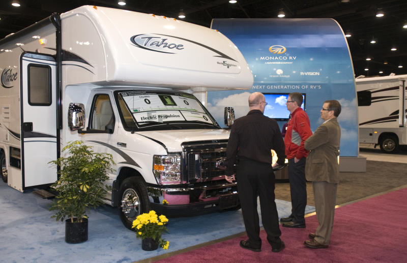 FILE - In this Tuesday, Nov. 29, 2011, file photo, attendees look at the all-electric E-Tahoe by MPV, at the Recreation Vehicle Industry Association's 49th Annual National RV Trade Showin Louisville, Ky.  Recreational Vehicle makers are churning out higher numbers of travel trailers bound for dealers' lots and, ultimately, campgrounds. Overall shipments from manufacturers to dealers are expected to rise 10 percent in 2012 and could gain another 4.5 percent next year, the Recreation Vehicle Industry Association said Tuesday, Nov. 27, 2012. (AP Photo/Brian Bohannon)