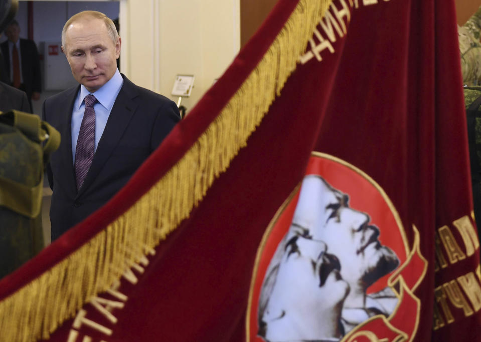 """Russian President Vladimir Putin looks at a Soviet era banner depicting Soviet Union founder Vladimir Lenin and Soviet dictator Joseph Stalin during his visit to the company """"Polyot"""", manufacturing parachute systems, in Ivanovo, 254 kilometers (158 miles) northeast of Moscow, Russia, Friday, March 6, 2020. Russian President Vladimir Putin said Friday he doesn't want to scrap presidential term limits or resort to other suggested ways of extending his rule, but otherwise he kept mum about his plans. (Alexei Nikolsky, Sputnik, Kremlin Pool Photo via AP)"""