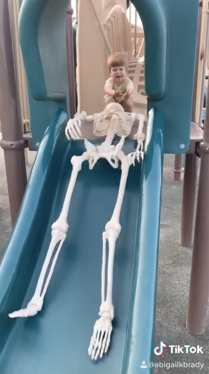 Toddler pushes skeleton down a slide. (abigailkbrady / Instagram)
