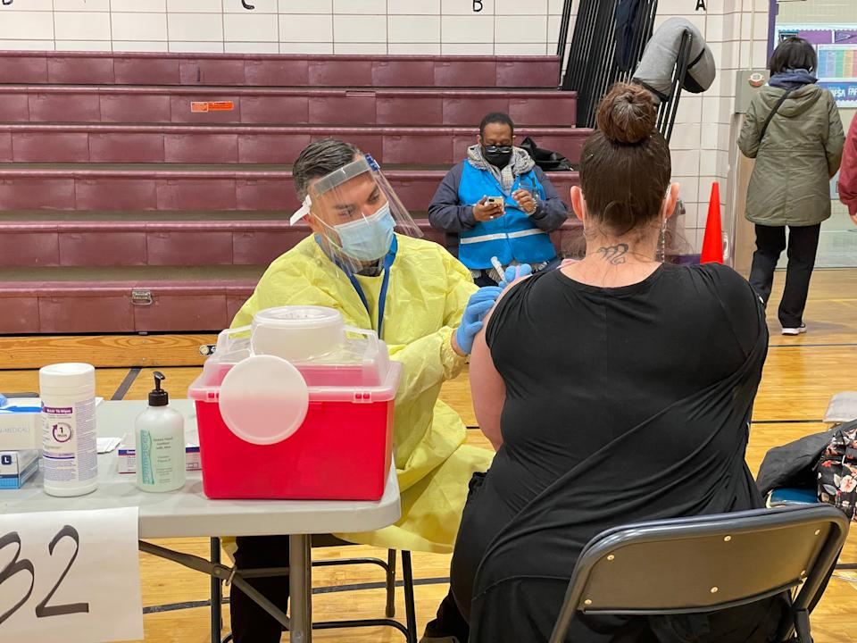 A New York teacher receives the first dose of Moderna's Covid-19 vaccine on Tuesday, 13 January, at one of New York City's new vaccination hubs (Danielle Zoellner/The Independent)