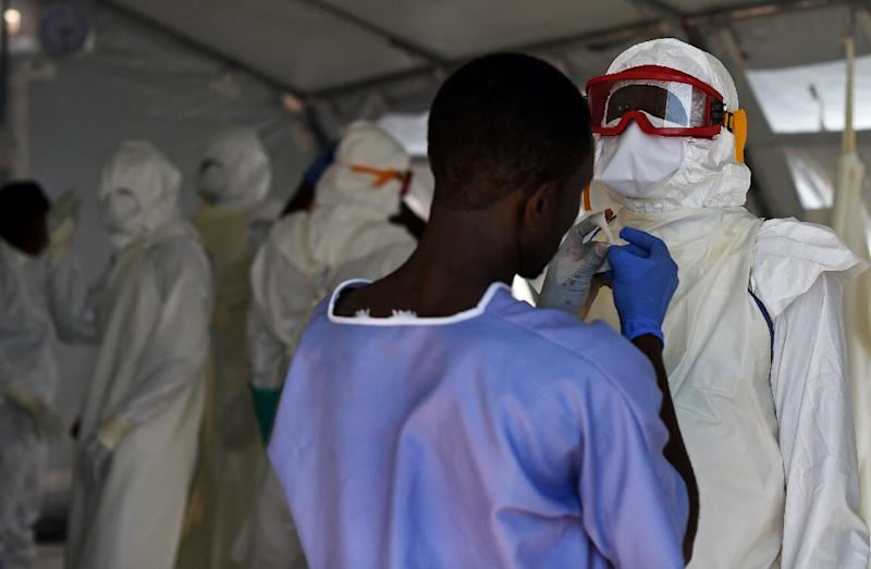 Health workers put on their personal protective equipment in the Kenama treatment centre run by the Red Cross Society on November 15, 2014 in Kenema, Sierra Leone (AFP Photo/Francisco Leong)