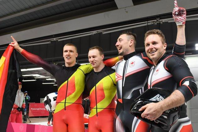 Germany's Francesco Friedrich, left, and Thorsten Margis, second left, celebrate with Canada's Alexander Kopacz, second right, and Justin Kripps after tying for gold in the two-man bobsled.
