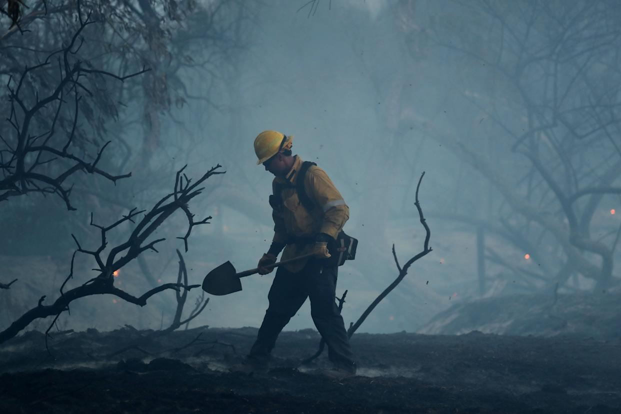 A firefighter works to put out hot spots on a fast moving wind-driven wildfire in Orange, California.