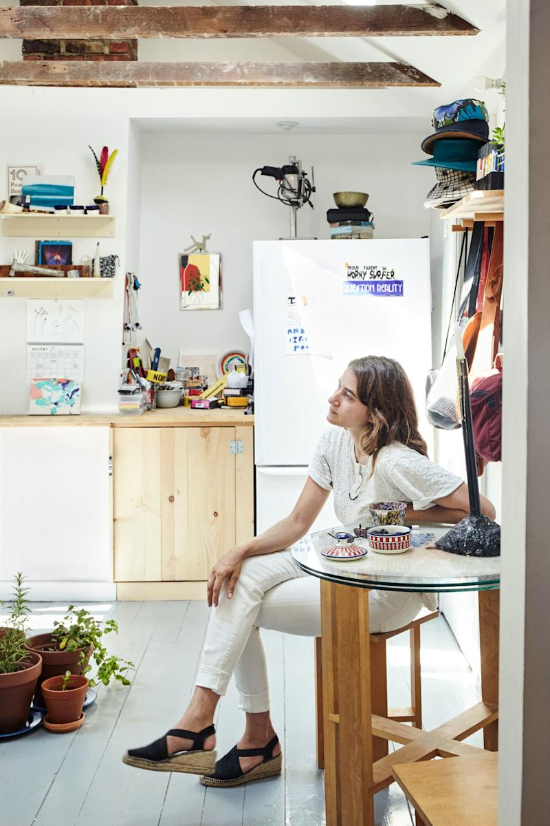 Elise in her eclectic DIY kitchen, where a little grouping of plants sits in the center of the floor.