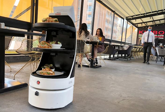 """'Mozo', a robot waiter of MARSES Robotic Solutions, serves food at Kimbo Restaurant & Cafe in Cairo, Egypt, on July 28, 2020. <p class=""""copyright"""">REUTERS/Ahmed Fahmy</p>"""