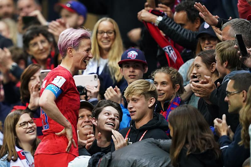 United States' forward Megan Rapinoe (L) celebrates with supporters after winning the France 2019 Women's World Cup Group F football match between USA and Thailand, on June 11, 2019, at the Auguste-Delaune Stadium in Reims, eastern France. (Photo by Lionel BONAVENTURE / AFP) (Photo credit should read LIONEL BONAVENTURE/AFP/Getty Images)