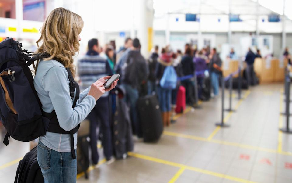 Traveller texting at airport check-in desk - Andrew Bret Wallis/Getty