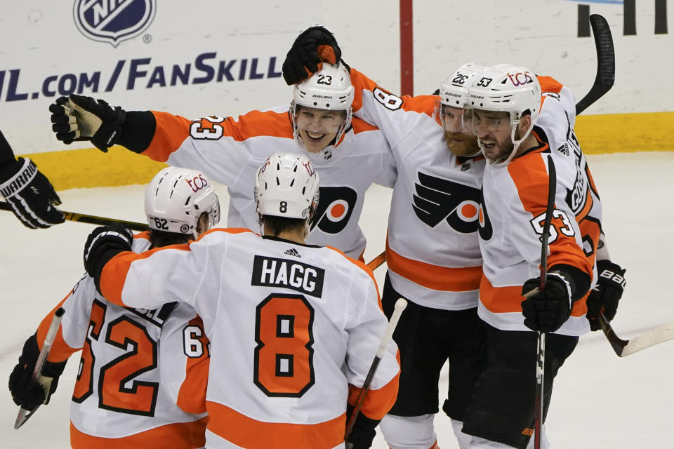 Philadelphia Flyers' Claude Giroux, second from right, celebrates with teammates after scoring goal against the Pittsburgh Penguins during the third period of an NHL hockey game Thursday, March 4, 2021, in Pittsburgh. (AP Photo/Keith Srakocic)