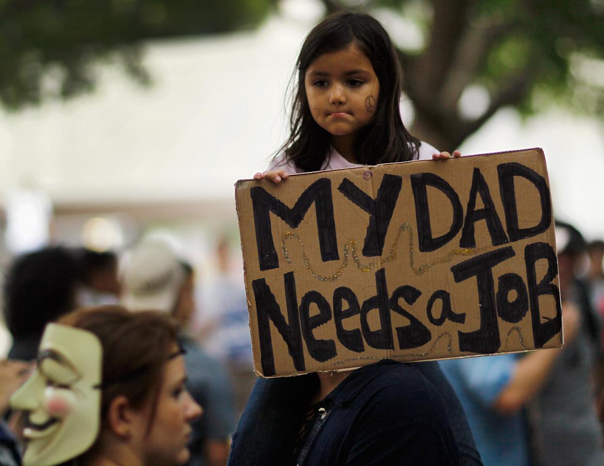 """MIAMI, FL - OCTOBER 15: Anabella Campuzano sits on the shoulders of her father, Camilo Campuzano as she holds a sign that reads,"""" My Dad Needs a Job""""' as they particpate in an Occupy Miami protest on October 15, 2011 in Miami, Florida. Thousands of people are taking to the streets in cities across the world today in demonstrations inspired by the 'Occupy Wall Street' protests in New York City, an estimated 1,000 people showed up to participate in the Miami protest.  (Photo by Joe Raedle/Getty Images)"""