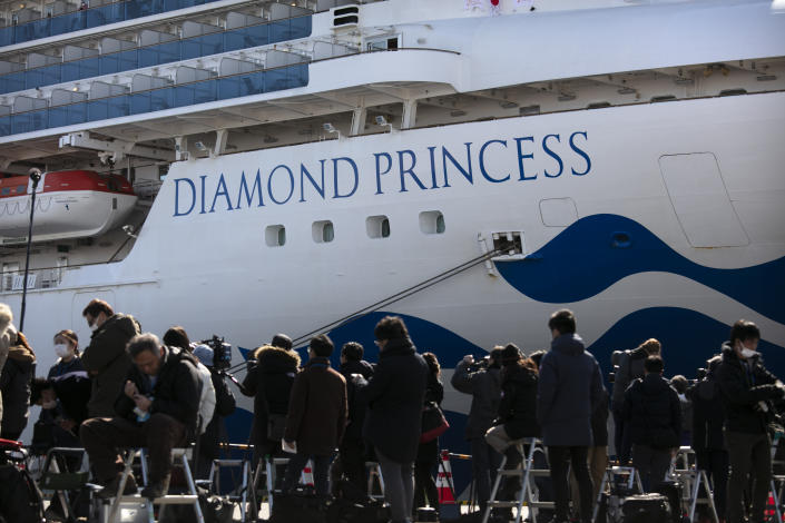 Media gather outside the quarantined Diamond Princess where life on board the luxury cruise ship is mixed (AP)