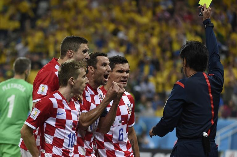 Croatia's Luka Modric (front), Darijo Srna (3rd L) and Dejan Lovren (2nd R) react as Japanese referee Yuichi Nishimura gives a penalty to Brazil during the World Cup opening match at the Corinthians Arena in Sao Paulo on June 12, 2014
