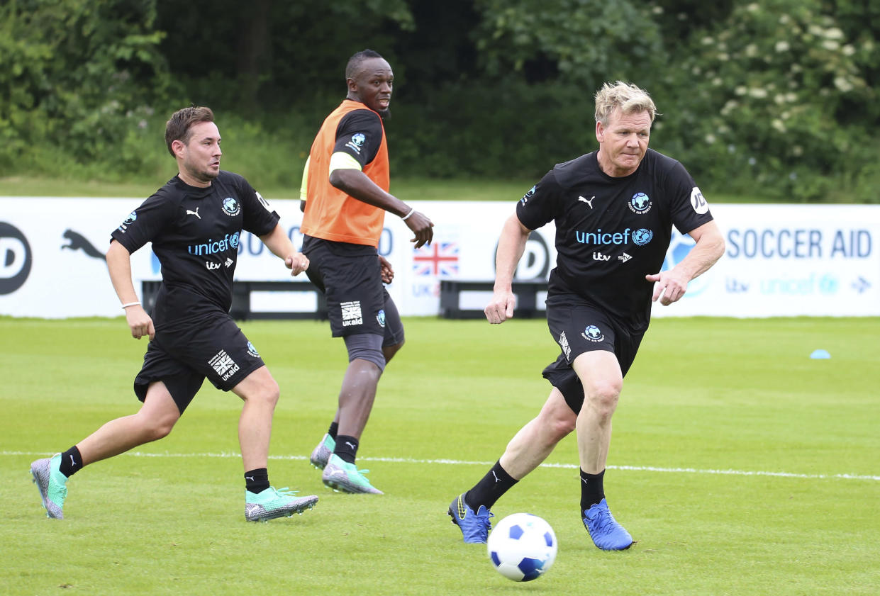 Martin Compston, Usain Bolt and Gordon Ramsay, from left, take part in the  World XI team's training session for Soccer Aid for UNICEF at Motspur Park, in London, Thursday June 7, 2018. (Isabel Infantes/PA via AP)
